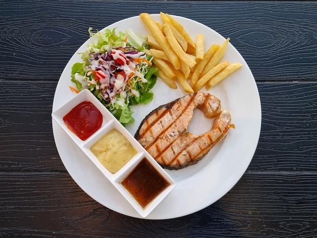 Trancio di salmone alla griglia con insalata di tre salse e patatine fritte su fondo di legno