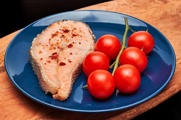 Trancio di salmone alla griglia con pomodori su un ramo. su un piatto blu e una tavola di legno