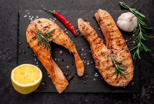 Bistecche di salmone alla griglia con spezie sul tavolo di pietra