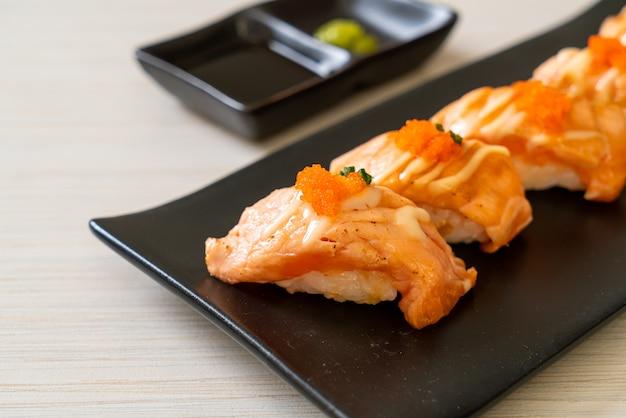 Sushi di salmone alla griglia sulla piastra nera - stile di cibo giapponese