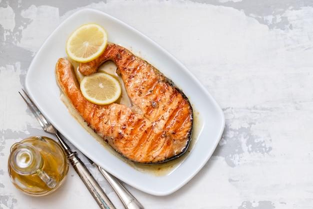 Salmone arrostito con il limone sul piatto