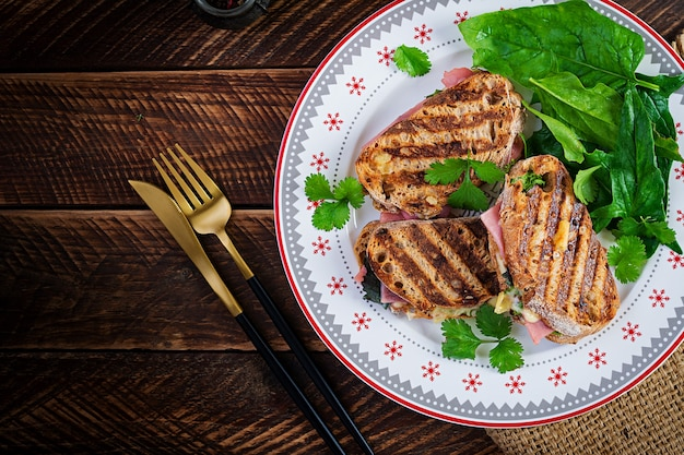 Panini alla griglia con prosciutto, pomodoro, formaggio e spinaci. deliziosa colazione o spuntino. vista dall'alto, copia spazio, sovraccarico