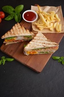Alla griglia e panino con pancetta, uovo fritto, pomodoro e lattuga serviti sul tagliere di legno