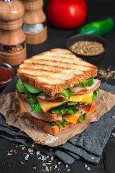 Sandwich alla griglia con prosciutto, formaggio e verdure fresche su uno sfondo scuro con ingredienti e spezie. vista verticale.