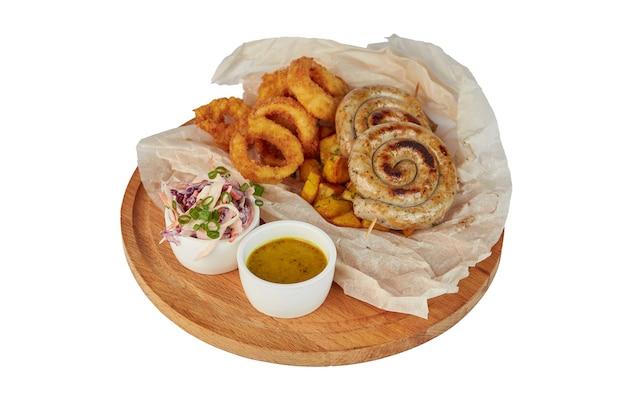 Salsiccia alla griglia con patate fritte e peperoni, ketchup, sul piatto bianco, isolato su bianco