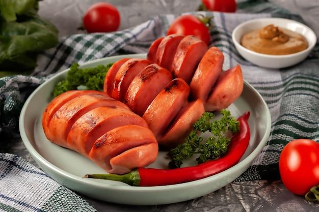 Salsicce alla griglia con verdure fresche su un vassoio