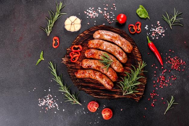 Salsicce alla griglia con verdure e spezie su fondo nero