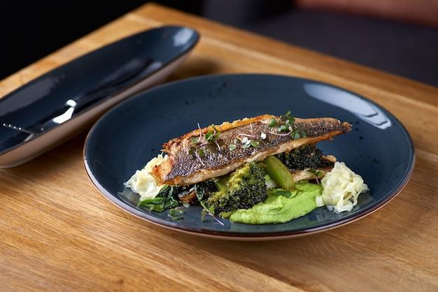 Branzino alla griglia con broccoli e purea di piselli su un tavolo di legno