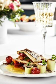 Branzino alla griglia con pomodorini saltati, servito con polpetta di patate su piatto bianco, contorno di filetto di branzino su fondo chiaro.