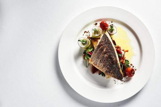 Spigola alla griglia con vista dall'alto di verdure, primo piano, piatto bianco, sfondo chiaro, copia spazio.