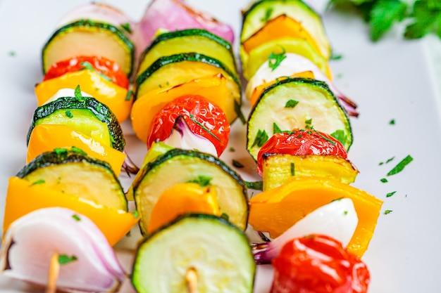Spiedini di verdure alla griglia su un piatto rettangolare grigio. concetto di cibo vegano.