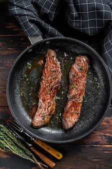 Gonna alla griglia bistecca machete in padella. fondo in legno scuro. vista dall'alto.