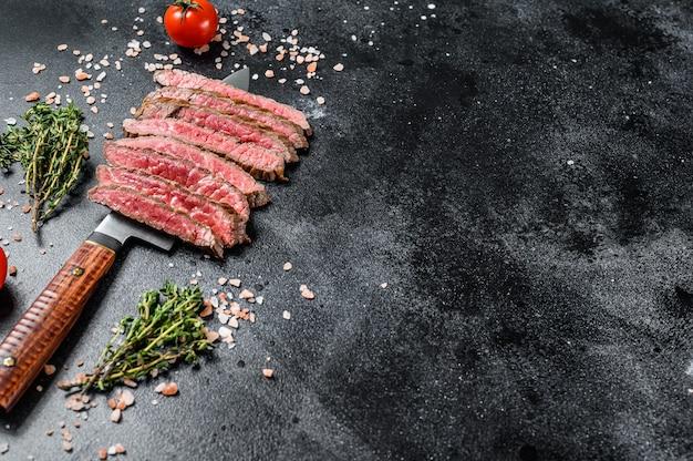 Bistecca rara di fianco alla griglia e affettata. carne di manzo marmorizzata. sfondo nero. vista dall'alto. copia spazio.