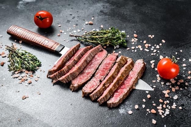Bistecca rara di fianco alla griglia e affettata. carne di manzo marmorizzata. sfondo nero. vista dall'alto.