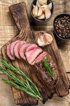 Bistecca di carne di filetto di agnello affettata alla griglia su un tagliere