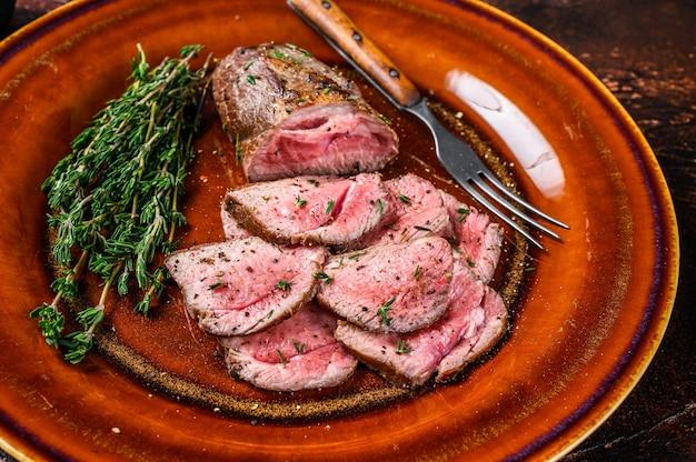 Bistecca di carne di filetto di agnello alla griglia e affettata su un piatto