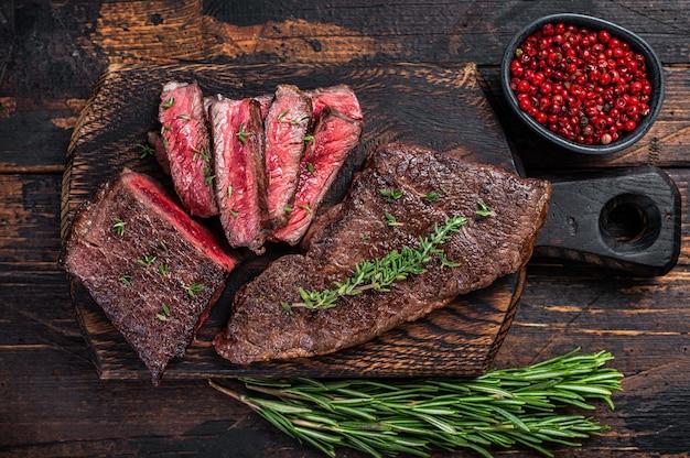 Bistecca di carne di manzo alla griglia gonna affettata su un tagliere con erbe aromatiche. fondo in legno scuro. vista dall'alto.