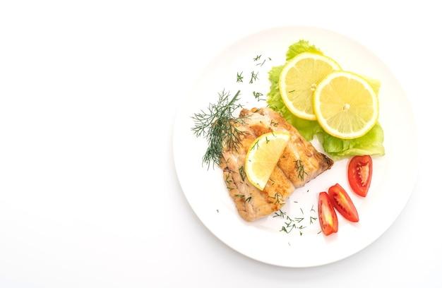 Bistecca di pesce dentice alla griglia con vagetable isolato sul tavolo bianco