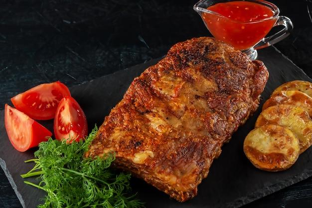 Costolette piccanti alla griglia servite con salsa di peperoncino piccante e pomodori freschi