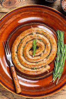 Salsiccia a spirale alla griglia di carne di maiale e manzo su un piatto rustico. fondo in legno. vista dall'alto.