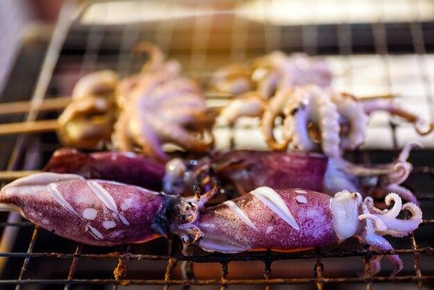 Calamari alla griglia su una stufa a carbone caldo nel mercato del cibo di strada