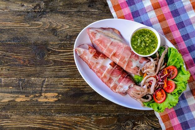 Calamari alla griglia in un piatto bianco, con salsa di frutti di mare, pomodori, rape