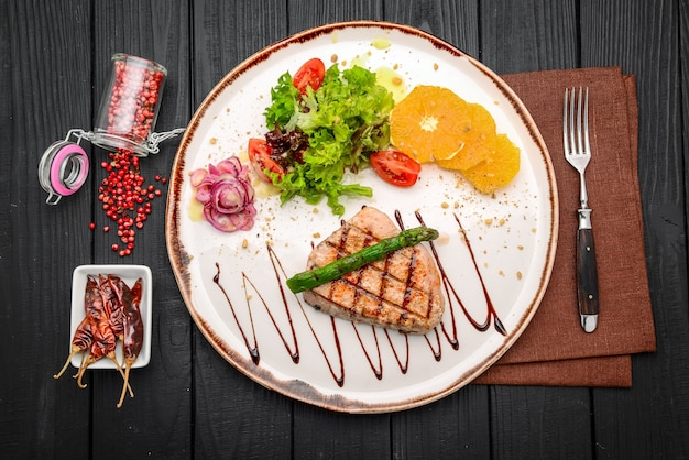 Bistecca alla griglia e asparagi su un piatto in un ristorante