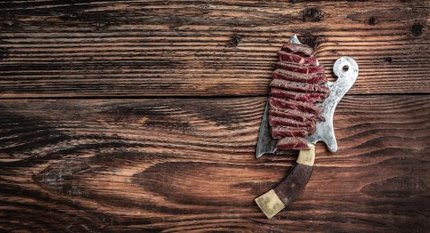 Bistecca alla griglia sul coltello da macellaio di carne. banner, posto ricetta menu per testo, vista dall'alto.