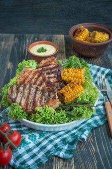 Bistecca alla griglia in una ciotola rotonda con spezie, erbe e verdure su un legno scuro
