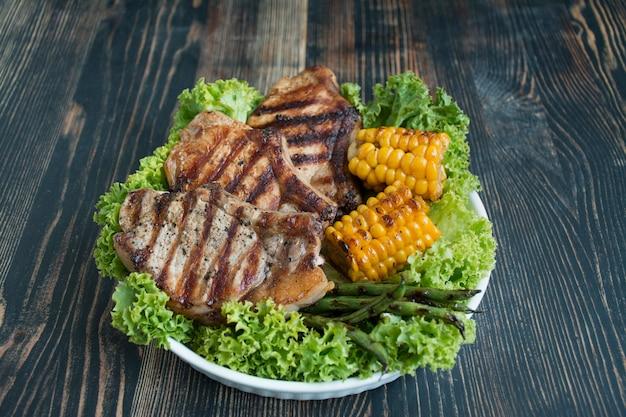 Bistecca alla griglia in una ciotola rotonda con spezie, erbe e verdure su un buio