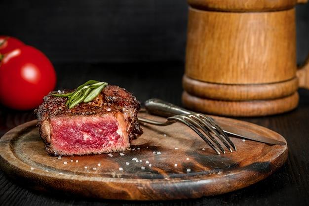 Bistecca alla griglia condita con spezie ed erbe fresche servita su un tagliere di legno con boccale di birra in legno...