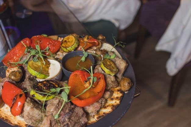 Filetto di manzo alla griglia e salsa di pepe su tagliere su fondo di legno scuro.