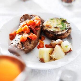 Bistecca alla griglia con patate e funghi ripieni