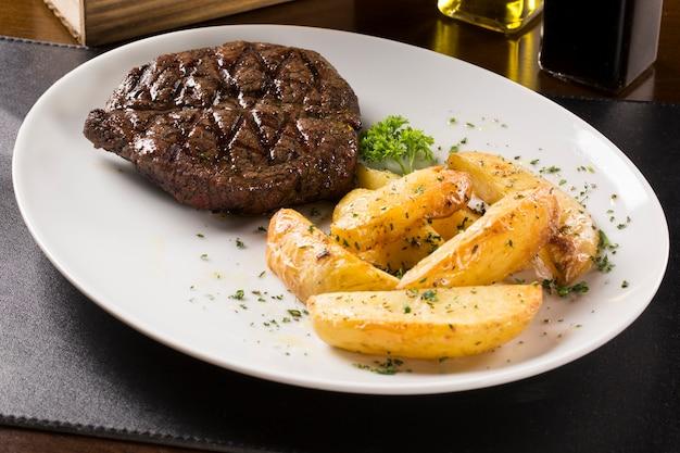 Bistecche alla griglia, patate al forno e insalata di verdure.
