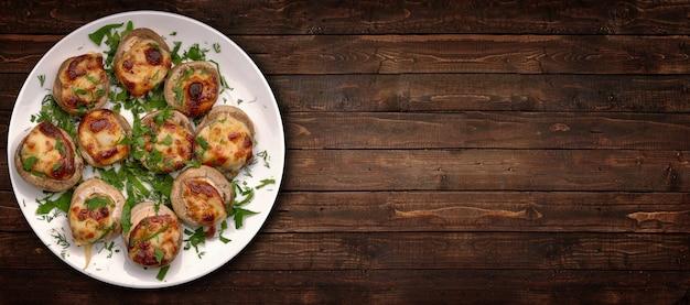 Funghi prataioli ripieni alla griglia con formaggio ed erbe aromatiche, su uno sfondo di legno