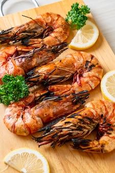 Gamberi tigre alla griglia o gamberetti con limone su tavola di legno