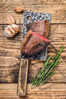 Bistecca di carne di manzo con cappuccio di controfiletto alla griglia su una mannaia. fondo in legno. vista dall'alto.