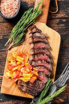 Cappuccio di controfiletto alla griglia o bistecca di picanha su un tagliere con erbe aromatiche. . vista dall'alto.