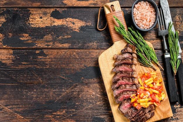 Cappuccio di controfiletto o bistecca di picanha alla griglia su un tagliere con erbe aromatiche