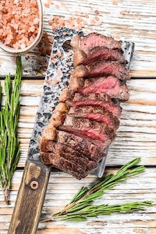 Controfiletto alla griglia o bistecca di picanha su una mannaia con erbe aromatiche. vista dall'alto bianco.