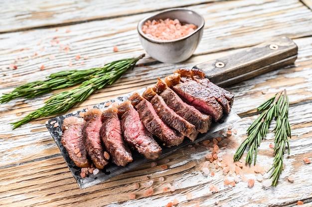 Cappuccio di controfiletto alla griglia o bistecca di picanha su una mannaia con erbe aromatiche. fondo in legno bianco. vista dall'alto.