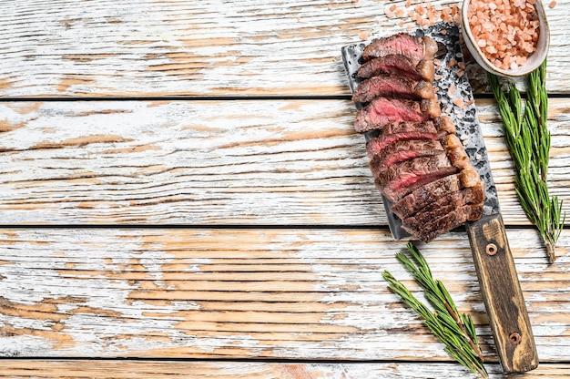 Controfiletto alla griglia o bistecca di picanha su una mannaia con erbe aromatiche