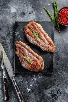 Cappuccio di controfiletto alla griglia o bistecca di picanha su un tagliere di pietra. sfondo nero. vista dall'alto.