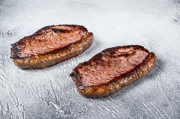 Protezione superiore del controfiletto alla griglia o bistecca di picanha su bianco. vista dall'alto.