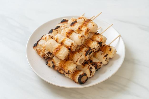 Torta di pasta di pesce a forma di tubo alla griglia o spiedino di calamari su piatto