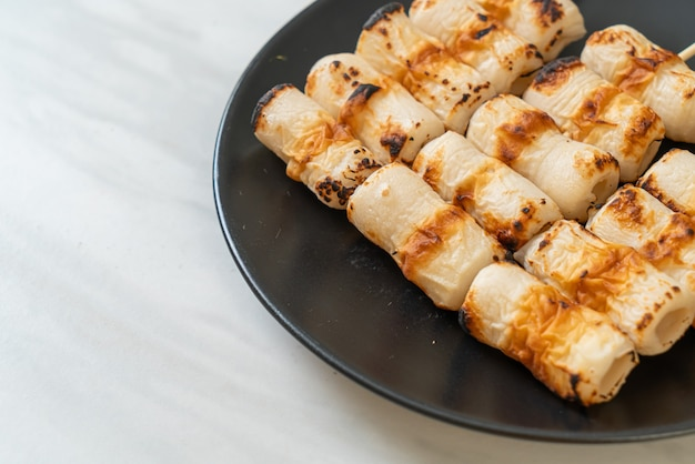 Tortino di pasta di pesce a forma di tubo alla griglia o spiedino di calamari su piatto