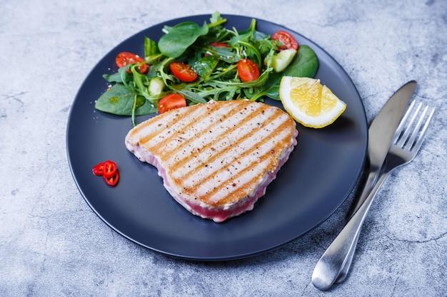 Tagliata di tonno alla griglia con verdure fresche, rucola, spinaci e limone. avvicinamento.