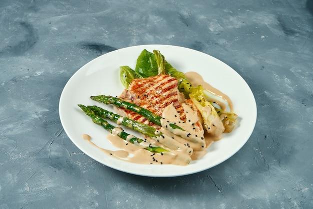 Bistecca di tacchino alla griglia con asparagi e salsa nel piatto bianco sulla superficie grigia
