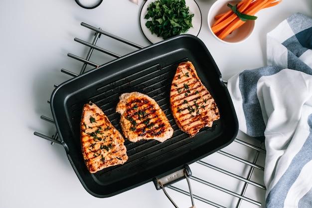 Bistecca di tacchino alla griglia con erbe e spezie in padella griglia nera sul tavolo.