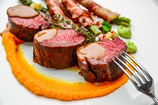 Filetto di vitello alla griglia con insalata, con asparagi e pancetta. sul tavolo di legno